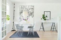 Filigraner Esstisch mit Klassikerstühlen vor grossformatigem Bild im Essbereich