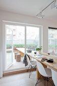 Langer Esstisch aus Holz mit weissen Klassikerstühlen im Essbereich, am Terrassenfenster