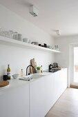 Lange, weisse Küchenzeile mit offenem Regal