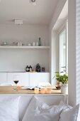Blick über weissem Sofa mit Kissen auf Esstisch und Küchenzeile