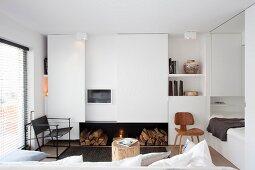 Einbauschrank mit Schiebetür und Schlafbereich in offenem, weissem Wohnraum