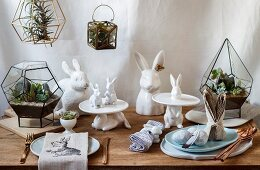 Easter arrangement of rabbit figurines and succulents in miniature terrariums