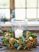 Lit candle in lantern surrounded by straw Easter wreath