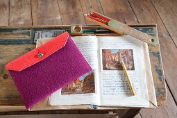 Knitted wool pencil case in red and purple on schoolbook on vintage school desk