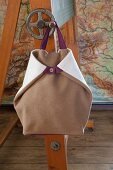 Light brown, hand-sewn, boiled-wool rucksack hanging from blackboard crank handle
