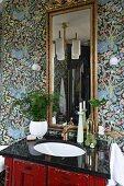 Houseplant on vintage washstand with black polished top below gilt-framed mirror