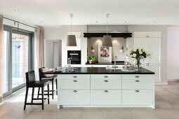 A white kitchen island with a black work surface and black, leather-covered bar stools