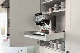 An open kitchen cupboard with an espresso machine on a pull-out tray