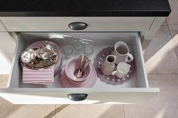 Pink crockery in an open drawer