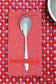 Spoon on red linen napkin and table mat made from red-painted wooden discs