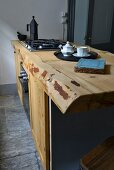Gas hob on solid wooden live-edge kitchen counter