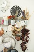 Various kitchen utensils and dried spices hung from vintage rack
