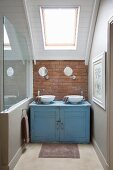 Battered blue washstand in niche under sloping ceiling