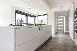 An island with white cupboards in an open-plan designer kitchen