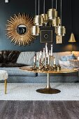Candlesticks on round coffee table below brass pendant lamps and sunburst mirror on blue wall