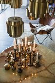 Brass candlesticks on round table below brass lampshades