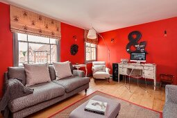 Lounge furniture and desk against red walls in renovated period apartment