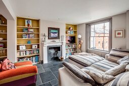 Upholstered furniture and fitted bookcases flanking open fireplace in comfortable living area