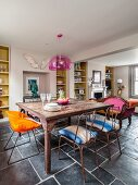 Vintage dinning table, metal chairs and retro chair in open-plan living area with fitted shelving