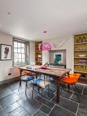 Vintage dining table, metal chairs and orange retro chairs in front of fitted shelving and lattice window