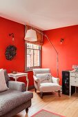 Comfortable antique reading chair and modern standard lamp in corner of room with red-painted walls