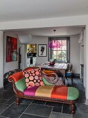 Art Nouveau chaise longue with colourful upholstery and scatter cushions in front of dining area
