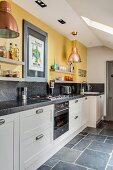 White kitchen counter with granite worksurface below shelves mounted on yellow wall