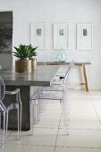 Concrete table and plexiglas chairs in modern dining room