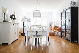 Dining table and vintage furniture on herringbone parquet flooring
