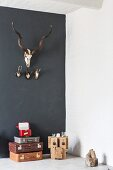Various hunting trophies on black wall above stack of retro suitcases and wooden sculpture