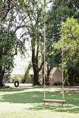 Swing in garden with mature trees
