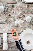 Hand hält Teelicht über rustikal gedeckten Weihnachtstisch