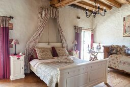 Bed with bed crown and rose-patterned textiles in romantic bedroom