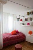 Ethnic bedspread in shades of red, white wall-mounted shelves and floating cabinet