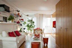 Einzimmerwohnung mit Einbauküche und orangefarbenen Hockern, weissem Hussensofa und Grünpflanze