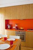 Gedeckter Esstisch vor Einbauküche mit Holzfronten und orangefarbenem Spritzschutz