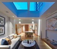 Illuminated living room with skylight at twilight