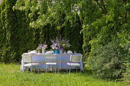 Table festively set in blue and white in summer garden