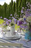 Blau-weiß gedeckter Gartentisch mit Blumensträußen