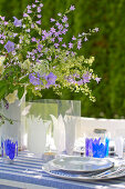 Gedeckter Gartentisch mit Glockenblumen-Deko