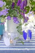 Mit Glockenblumenmotiv beklebte Windlichter vor Blumenstrauß