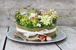 Autumnal flower arrangement in cake tin decorated with antler and horse chestnuts