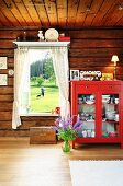 Red dresser next to window with garden view in wooden house