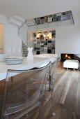 Weisser Esstisch und Plexiglas-Stühle in offenem Wohnbereich eines Architektenhauses