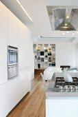Weisse Designerküche mit Kochinsel in offenem Wohnbereich eines Architektenhauses