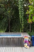 Wood-clad pool edging and colorful towel in front of densely grown green plants