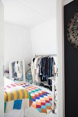 Colourful crocheted rug, clothes rack and mirror in bedroom