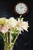 Exotic bouquet in front of clock on black wall