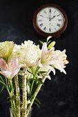 Exotischer Blumenstrauß vor schwarzer Wand mit Uhr