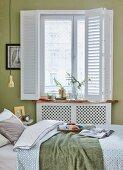 Frühstückstablett auf Bett und vor Fenster mti weißem Scheibenvorhang im Schlafzimmer mit grüngetönter Wand
